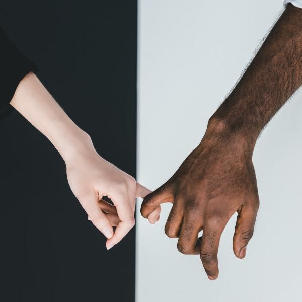 black and white hands holding fingertips